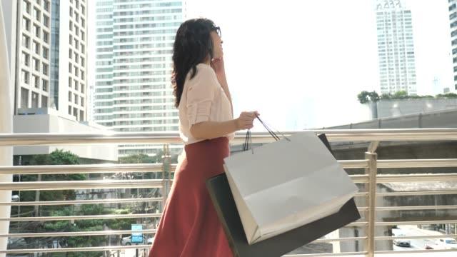 Asian woman walks with shopping bags in the trade center
