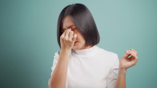 Asian woman was sick with eyes pain and standing isolated over blue background. Health care concepts. 4k video. video