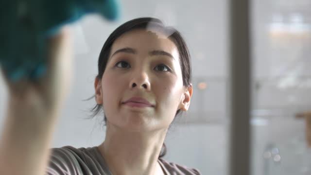 asian woman washes and wipes the windows of the house - zagadnienia filmów i materiałów b-roll
