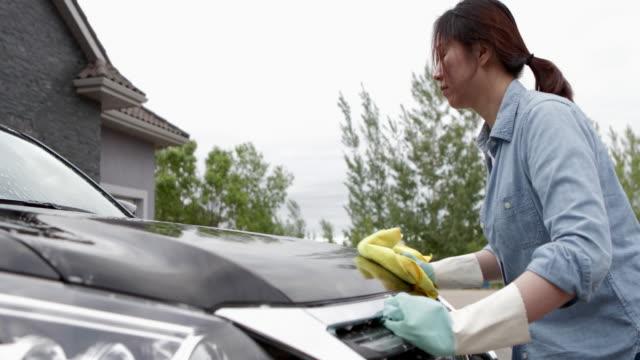 Video asian woman washing car at yard