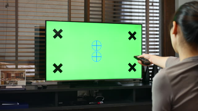 Asian woman watches television Green screen on living room video
