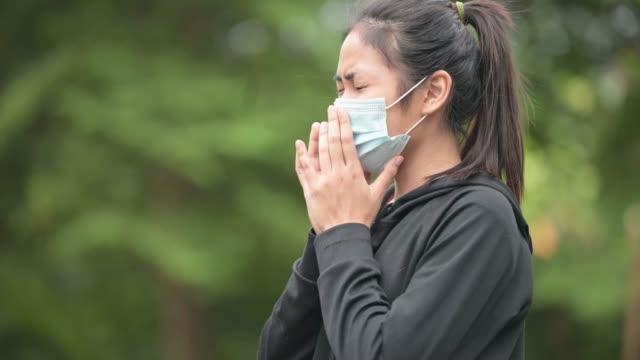 asiatische frau tragen gesichtsmaske hatte einen husten und brustschmerzen, während auf das haus beschränkt - patientin stock-videos und b-roll-filmmaterial