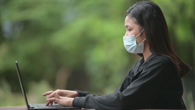 asiatische frau tragen gesichtsmaske arbeit von zu hause, die andere ecke im garten während der quarantäne von der coronavirus-pandemie - patientin stock-videos und b-roll-filmmaterial