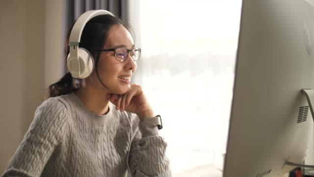 아시아 여자 착용 헤드폰 사용 컴퓨터 에 홈 - 한 명의 젊은 여자만 스톡 비디오 및 b-롤 화면