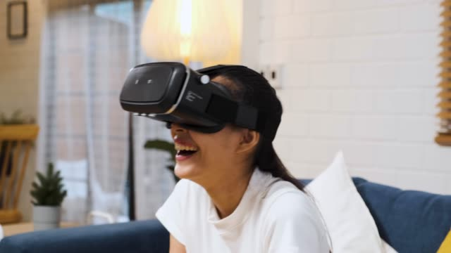 Asian woman wear vr headset glasses and play virtural reality  sitting on sofa at home.digital tehcnology lifestyle..