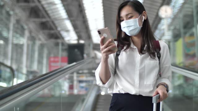 空港で携帯電話を使用してフェイスマスクを身に着けているアジアの女性 - 乗客点の映像素材/bロール