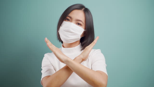 Asian woman wearing hygiene mask showing arms crossed stop sign and standing isolated over blue background. Health care concepts. 4k video. video