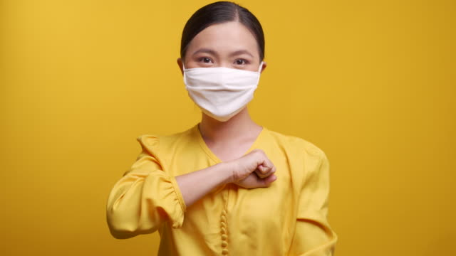 asian woman wearing protective face mask put her fist on a left chest isolated on yellow background. - rispetto video stock e b–roll