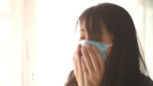 vídeos y material grabado en eventos de stock de mujer asiática usando mascarilla quirúrgica y tosiendo con caja fuerte - ojo morado