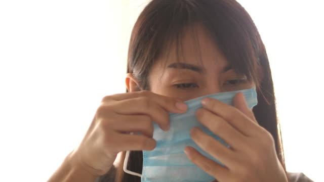 vídeos y material grabado en eventos de stock de mujer asiática usando máscara quirúrgica para proteger el virus - ojo morado