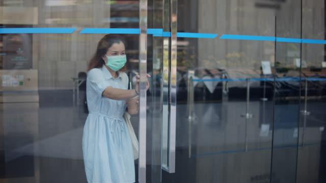 vidéos et rushes de la femme asiatique avec une tasse de café ouvre la porte et marchant hors de l'immeuble de bureau, mouvement lent - porte entrée