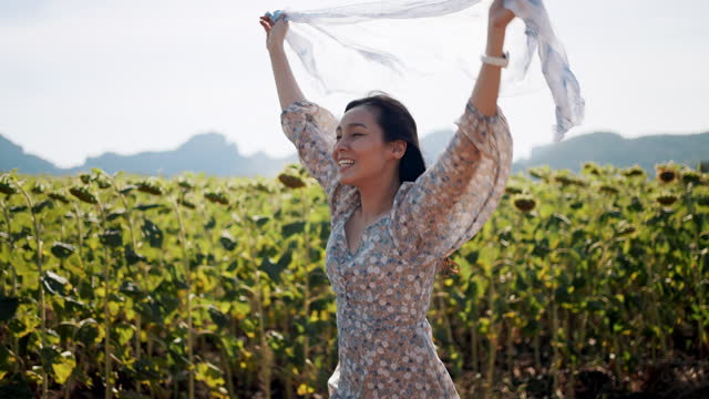 Asian Woman with chiffon scarf running on summer field