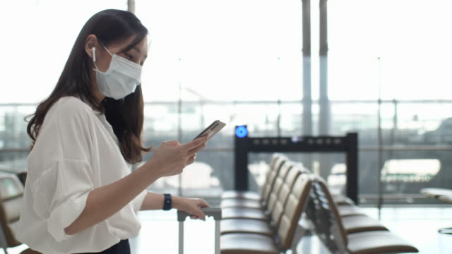 Asian Woman with Face mask using mobile phone while walking to Travel at airport, Slow motion