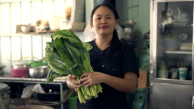 asiatische frau mit grünem gemüse lächelnd - grünkohl stock-videos und b-roll-filmmaterial