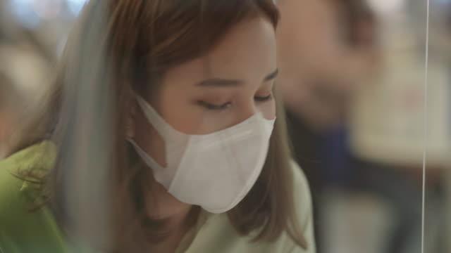 vídeos y material grabado en eventos de stock de mujer asiática con máscara higiénica y trabajando mientras que el distanciamiento social - shield