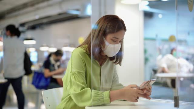 衛生的なマスクを持ち、カフェでスマートフォンを使用しているアジアの女性 - 飲食店点の映像素材/bロール