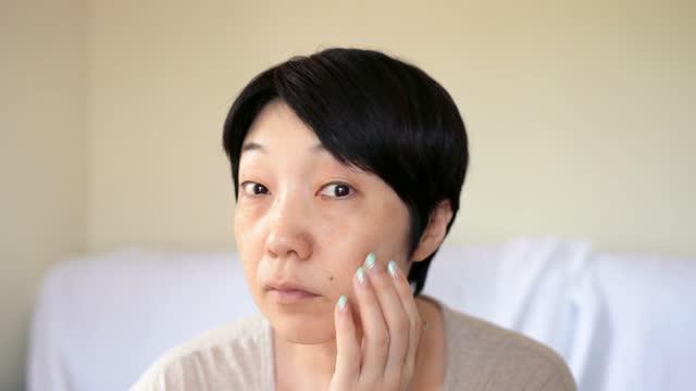 ノーメイクのアジアの女性 鏡を見て - 人の肌点の映像素材/bロール