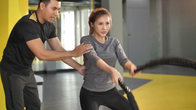 asian woman with personal trainer working out with battle ropes in gym - personal trainer stock videos and b-roll footage