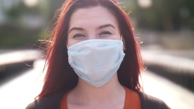 donna asiatica con maschera protettiva per il viso all'aperto. - capelli rossi video stock e b–roll