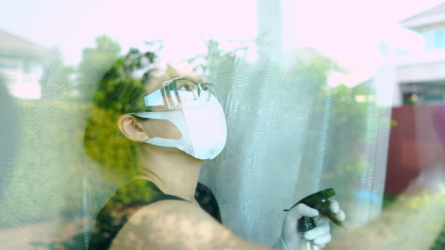 asian woman with safety glasses and face mask with hand glove using spraying alcohol and cleaning the window - hand on glass covid video stock e b–roll