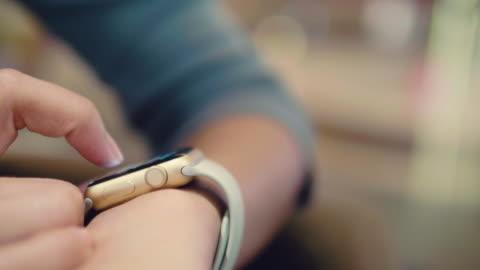 vídeos de stock e filmes b-roll de asian woman with smart watch on sofa. - consumismo