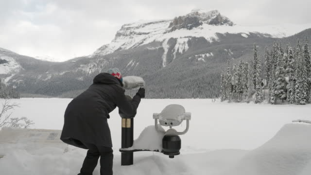asian woman with telescope at emerald lake