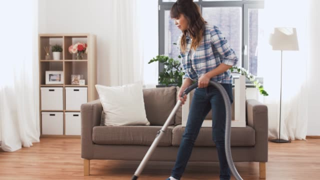 evde elektrikli süpürge ile asya kadın - ev temizleme stok videoları ve detay görüntü çekimi