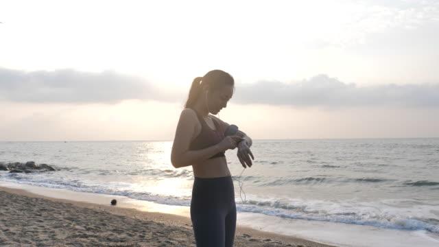 asian woman woman using smart watch on beach - computer indossabile video stock e b–roll