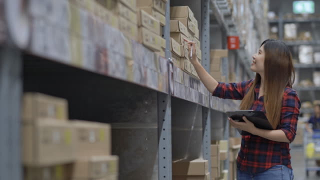 Asian woman worker checking stock in warehouse inventory