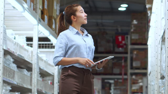 asian woman worker working using tablet checking boxes logistic import and export supplies packages in warehouse , logistics concept - prodotti supermercato video stock e b–roll