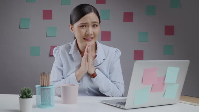 Asian woman working at home office holding hands in prayer and looking at camera.