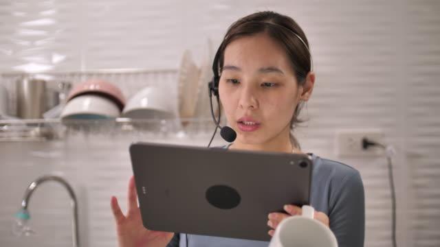 自宅で同僚と話している彼女のデジタルタブレットとビデオ会議に取り組んでいるアジアの女性 - テレビ会議 日本人点の映像素材/bロール