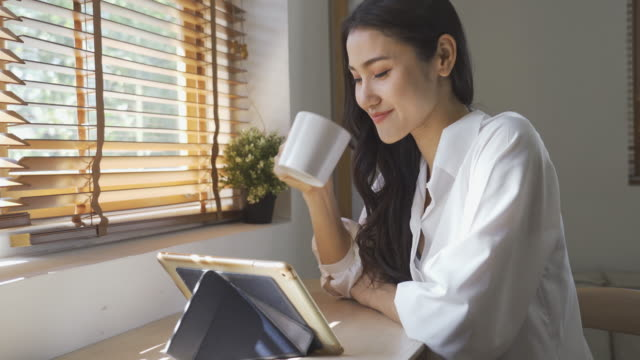 Asian woman working on tablet and drinking coffee Asian woman working on tablet and drinking coffee, 4k footage clip east asian ethnicity stock videos & royalty-free footage