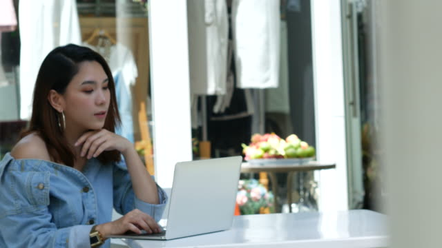 asian woman working online with laptop and smartphone - owner laptop smartphone video stock e b–roll