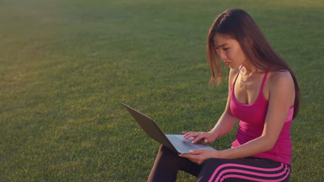 Asian woman working with laptop on green grass. Attractive woman using notebook video
