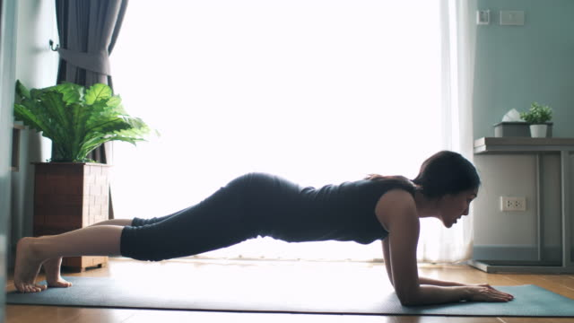 Asian Woman Workout Clothes is Doing a Plank Exercise