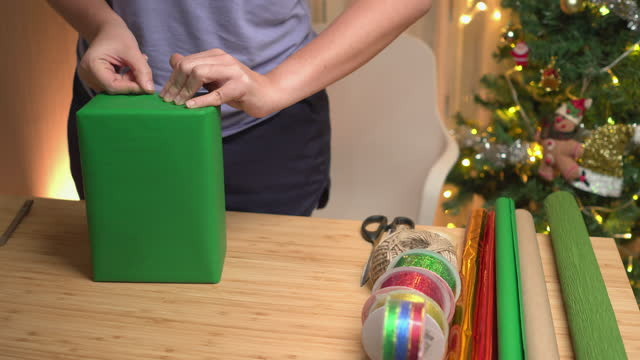 Asian woman's hand attaching with clear tape to warping brown gift box with green paper, Christmas  presents on the table at home at night with a utensil, ribbon paper in apartment decorated with Christmas tree and ornament