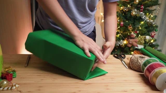 Asian woman's hand fold paper to warping brown gift box with green paper, attaching with clear tape, Christmas  presents on the table at home at night with a utensil, ribbon paper in apartment decorated with Christmas tree and ornament