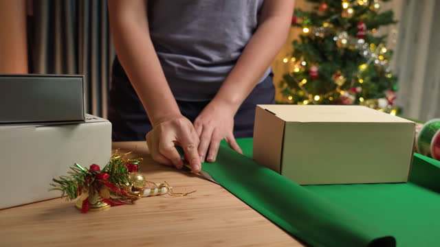 Asian woman's hand preparing a green paper, cutting it with a cutter for warping brown gift box, Christmas presents on the table at home at night with a utensil, ribbon paper in apartment decorated with Christmas tree and ornament, dolly shot