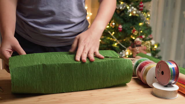 Asian woman's hand preparing a green paper to warp gift box, Christmas presents on the table at home at night with a utensil, ribbon paper in apartment decorated with Christmas tree and ornament