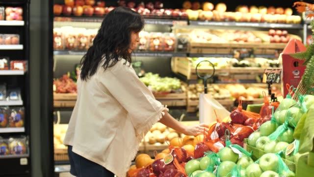 asian woman's hands take a vegetable in supermarket - prodotti supermercato video stock e b–roll