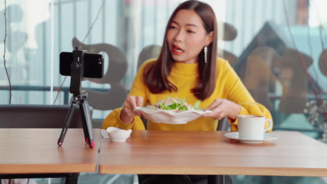 asian women aged 20-30 years, she was wearing a casual lifestyle and live my own vlog, tourism and restaurants, sitting on a table in a restaurant with live cameras. food and salad vegetables - tiktok стоковые видео и кадры b-roll