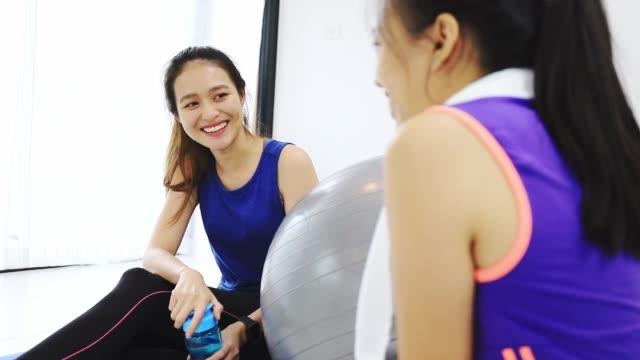 アジアの女性と友人が一緒に話し、コピースペースで自宅の背景でヨガや運動をした後に休憩。体重を減らし、柔軟性を高め、形状を引き締めるための運動。 - 有酸素運動点の映像素材/bロール