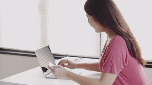 asian women are buying online with a credit card. asia girl are using laptop and doing online transactions.