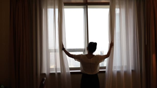 Asian women are staying in a hotel room.Open the curtain of window in the room looking to outside view.Travel in holidays concept.
