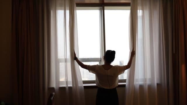 asiatische frauen übernachten in einem hotelzimmer. öffnen sie den vorhang des fensters im raum mit blick auf die außenansicht. reise im urlaub konzept. - eine reservierung vornehmen stock-videos und b-roll-filmmaterial