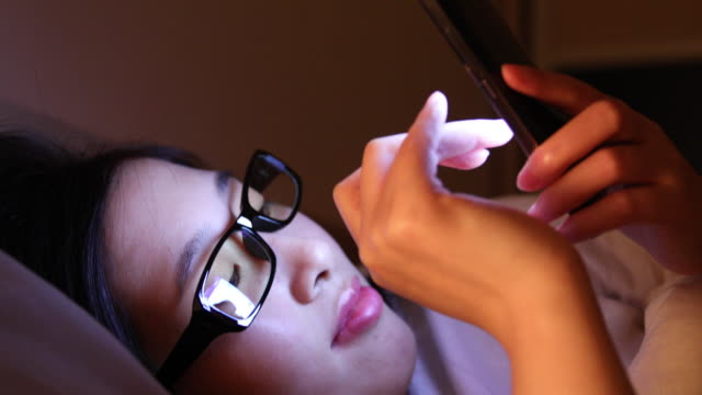 Asian women are using the smart phone on the bed video