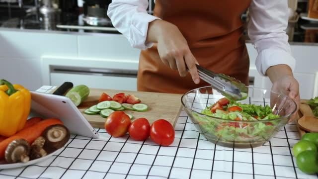 vídeos y material grabado en eventos de stock de las mujeres asiáticas están viendo recetas en una tableta para hacer ensaladas. - cáliz objeto religioso