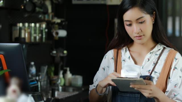 vídeos y material grabado en eventos de stock de las mujeres asiáticas barista sonriendo y usando café de la máquina y comprobar cuenta en café tienda contador - comida de trabajo mujer negocio pequeño propietario y beben café concepto - gerente de cuentas