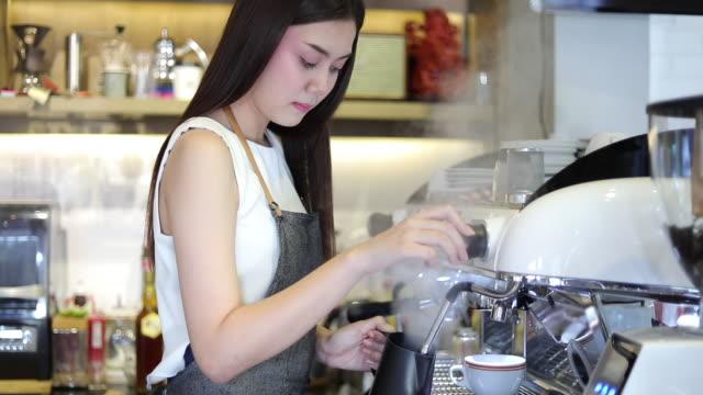 アジアの女性バリスタの笑顔しコーヒーのコーヒー マシンを使用してのショップ カウンター - 働く女性小企業所有者食べ物飲食カフェのコンセプト - バリスタ点の映像素材/bロール